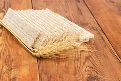 Multi-grain crispbread with wheat ears on wooden surface closeup Stock Photos