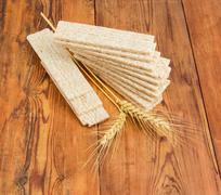 Multi-grain crispbread and wheat ears on wooden surface Stock Photos
