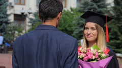 Man in suit congratulating his graduated girlfriend and presenting flowers Stock Footage