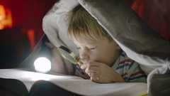 Little Boy Searching for Clues in Book Stock Footage