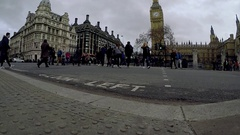 DRAMATIC CRANE SLOW MOTION SHOT PEOPLE CROSSING ROAD NEAR BIG BEN LONDON Arkistovideo