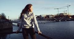 Beautiful smiling brunette girl taking off her jacket walking on bridge, river Stock Footage