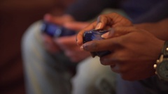 Video game console controller hands detail, played by two young men. Focus pull Stock Footage