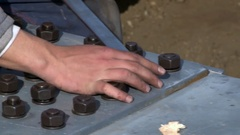 Worker with a wrench tighten screws fixing metal plates that make up an iron  Stock Footage
