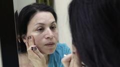 Woman in Mirror Looking at Her Skin Handheld Stock Footage