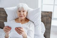 Cheerful granny keeping her tablet in hospital Stock Photos