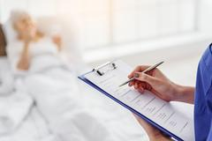 Doctor writing answers of grandmother in hospital Stock Photos