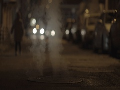 Steam rises from manhole street illuminated by the headlights of cars Stock Footage