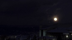 The moon rises over night houses covered with snow timelapse Stock Footage