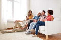 Happy friends with popcorn and beer at home Stock Photos