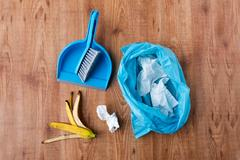 Rubbish bag with trash and cleaning items at home Stock Photos