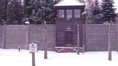 Steadicam shot of barbed wire fence and guard tower of a concentration camp in Stock Footage