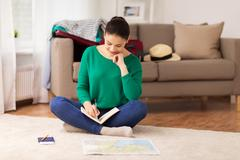 Woman with notebook and travel map at home Stock Photos