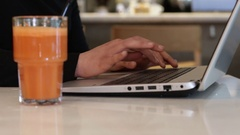Woman with carrot juice using laptop Stock Footage