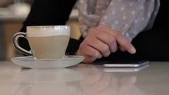 Using smartphone on coffeshop table Stock Footage