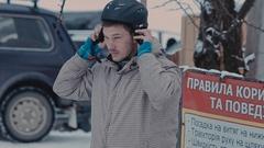 Guy wears a helmet for snowboarding Stock Footage