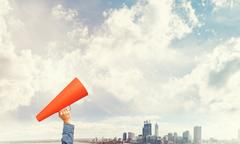Hand of man holding red paper trumpet against cityscape background Stock Photos