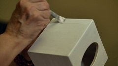 Old woman applies adhesive as a foundation of a wooden white box. Decoupage Stock Footage