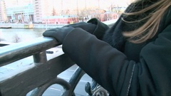 Girl hands in black gloves and jacket on the bridge railing, street view Stock Footage