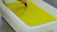 Woman hand mixes the liquid of yellow colour Stock Footage