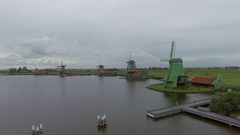 Riverside windmills and green field, aerial view Stock Footage