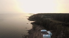Aerial view sand sea shore at forest with white tents and sports ground in Stock Footage