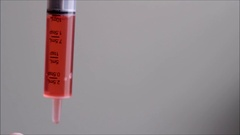 Dispensing red liquid medicine from a syringe Stock Footage