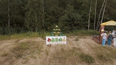 Aerial. Woman shoot plushy with slingshot at pyramid of blocks on edge of forest Stock Footage