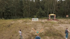 Aerial shot man plays irl angry birds with plushies and giant slingshot outside Stock Footage
