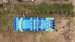 Aerial top shot topless man jumping on blue inflatable obstacle course on sand Stock Footage