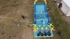 Aerial top shot women going through blue inflatable obstacle course on sand Stock Footage