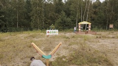 Aerial. People play real life angry birds with giant slingshot on edge of forest Stock Footage