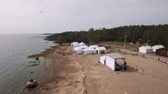 Aerial shot sandy beach on sea shore with white tents. Kite flying in sky Stock Footage