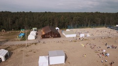 Aerial shot sandy beach with white tents and sports ground. Kite flying in sky Stock Footage