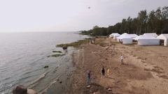 Aerial shot people fly kites on sandy sea shore with white tents in summertime Stock Footage