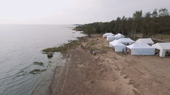Aerial shot people fly kites on wild sea shore with white tents in summertime Stock Footage