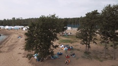 Aerial shot people laying on beanbags under trees on sandy shore in summertime Stock Footage