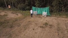 Air view man shooting bow arrows in bullseye target on forest edge in summertime Stock Footage