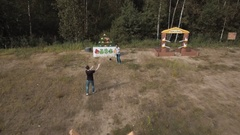 Aerial view two men playing giant slingshot game knocking down plushies outside Stock Footage