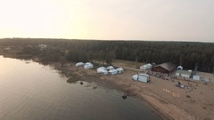 Aerial view sand beach near forest with white tents and sports ground in sunset Stock Footage