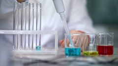 Scientist working with liquid in laboratory glassware. Test tubes filling liquid Stock Footage