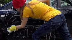 Female worker washing automobile in open air. Handheld shot Stock Footage