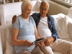 Senior couple looking at a photo album in living room Stock Footage