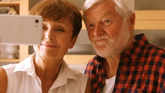 Senior couple taking selfie on mobile phone in kitchen Stock Footage