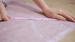 Hands of a seamstress. Seamstress tape measure applies to the fabric. Stock Footage