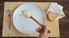 The man puts a fresh-brewed, steaming rice on white dish a wooden spoon Stock Footage