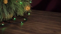 The man puts box of gift under the Christmas tree. Fir stand on the wooden table Stock Footage
