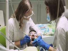 Dentists produce teeth cleaning man. 4k footage. Dental clinic. Close-up. Stock Footage