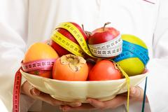 Woman holding fruits dietitian recommending healthy food. Stock Photos