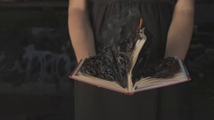 Woman with a burning book in hand Stock Footage